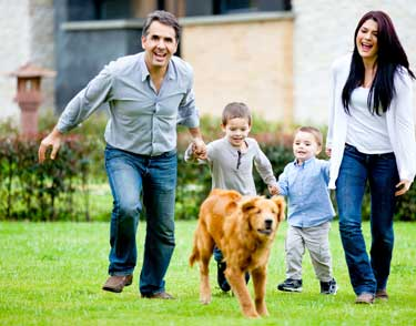 Family looking happy running with their dog.